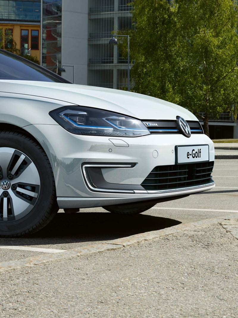 A white Volkswagen e-Golf electric vehicle parked in front of office buildings