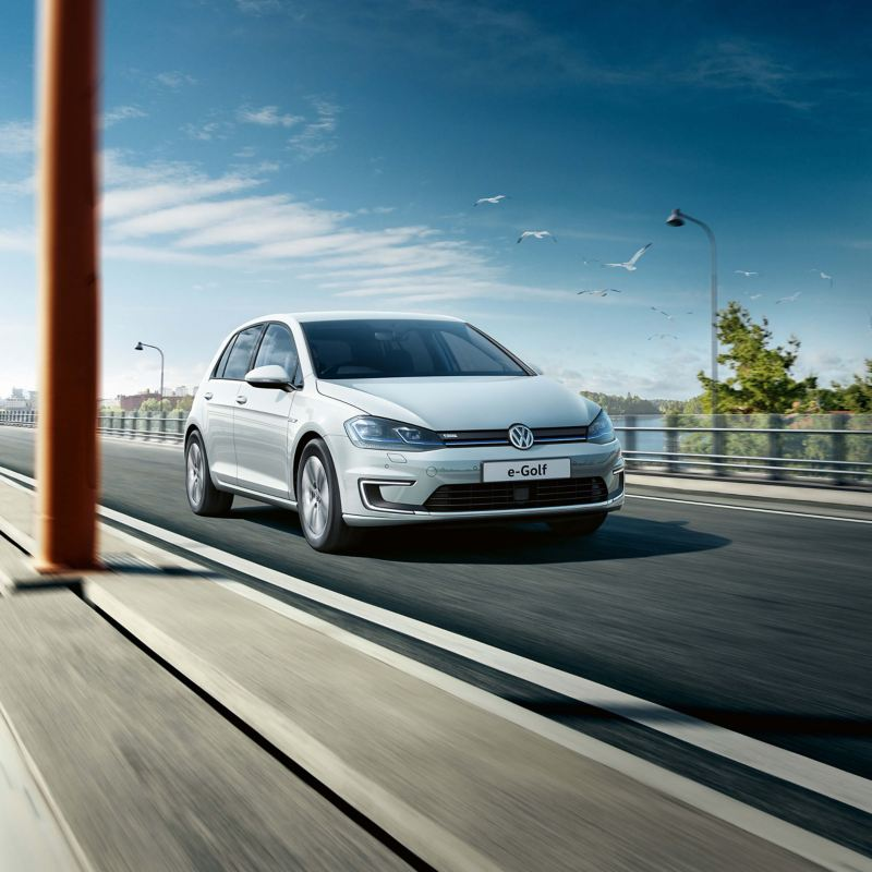 A white Volkswagen e-Golf driving across a bridge, bird flying overhead.