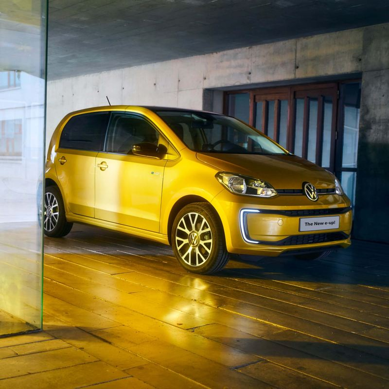A gold Volkswagen e-up! parked on a wooden floor with a concrete wall behind