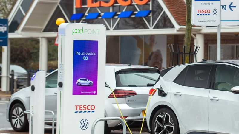 A Volkswagen e-Golf and an ID.3 electric vehicle charging in front of a TESCO.