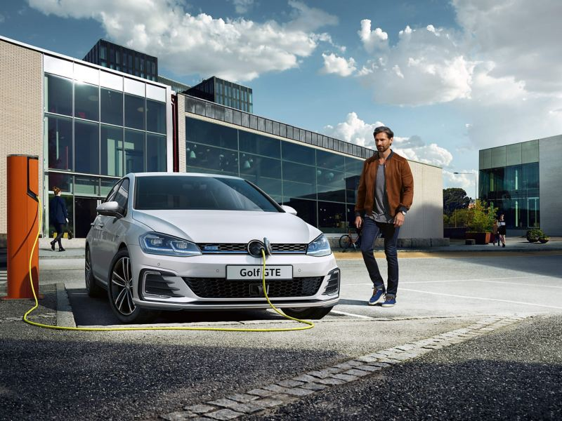 Man walking in front of a parked Volkswagen car charging