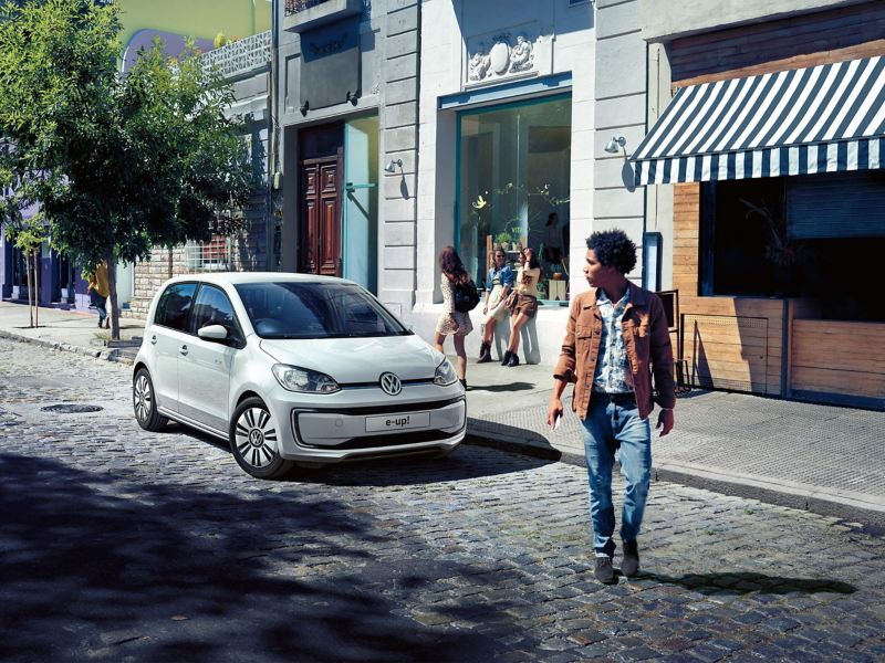 A white Volkswagen e-up! in a cobbled shopping street, pedestrians shopping.