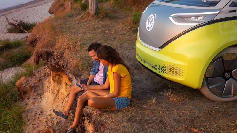 Couple sitting by a Volkswagen electric car, on a cliff face next to a beach.