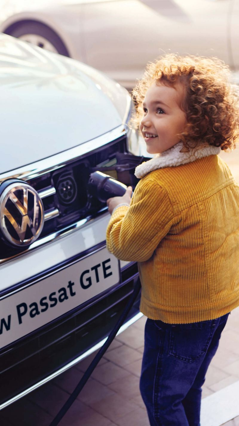 A young child connecting a plug to the front of a Volkswagen Passat GTE.
