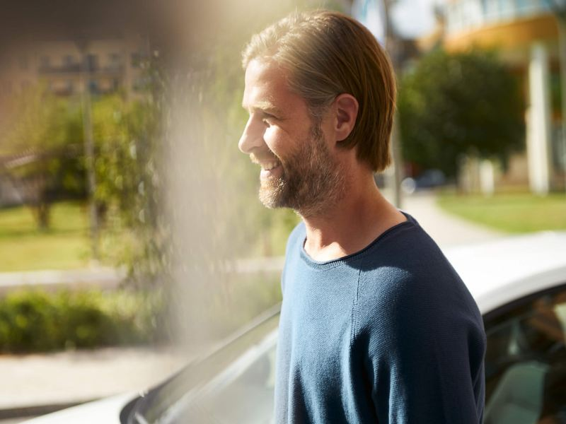 Man smiling next to his parked Volkswagen car