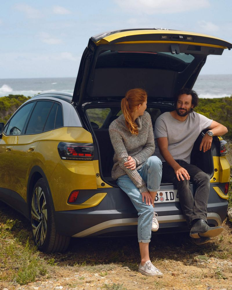 A couple sit in the open boot of the Volkswagen ID.4