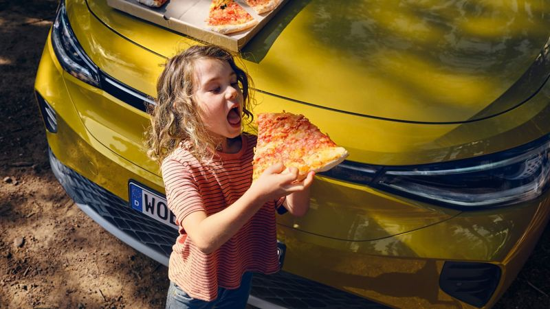 Young girl eating a pizza in front to the Volkswagen ID.4