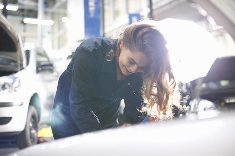 Mechanikerin untersucht Wagen