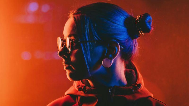Junge Frau steht im orangenen Licht und schaut zur Seite.