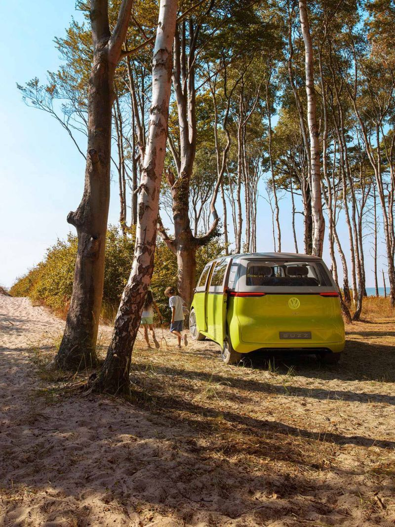 Ragazzi si allontano da ID Buzz VW parcheggiato in un bosco vicino al mare