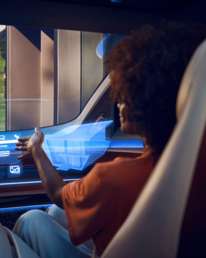 donna seduta nel lato passeggero interagisce con cockpit virtuale all'interno di ID Vizzion auto elettrica VW