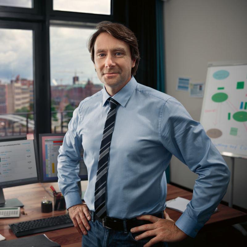 Ein Mann im Hemd steht vor einem Schreibtisch mit den Händen in die Hüfte gestützt