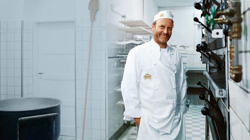 Ein Bäcker steht in einer Backstube.