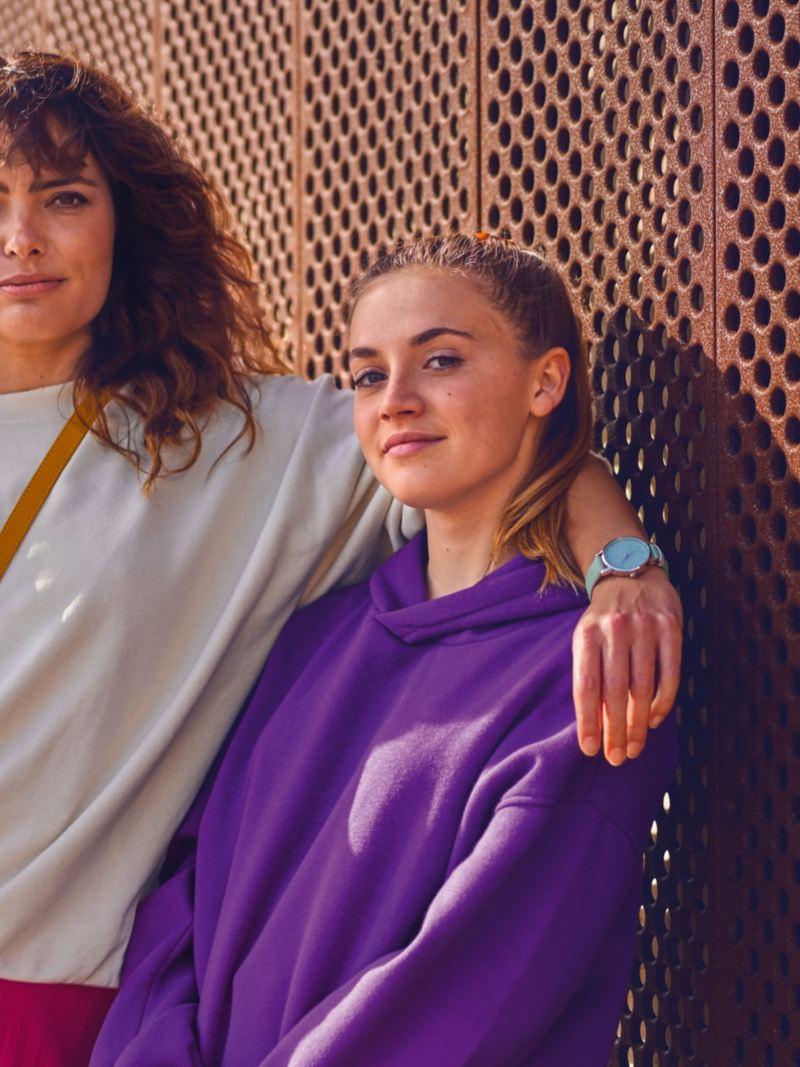 Mutter und Tochter stehen vor einer kupferfarbenen Lochwand.