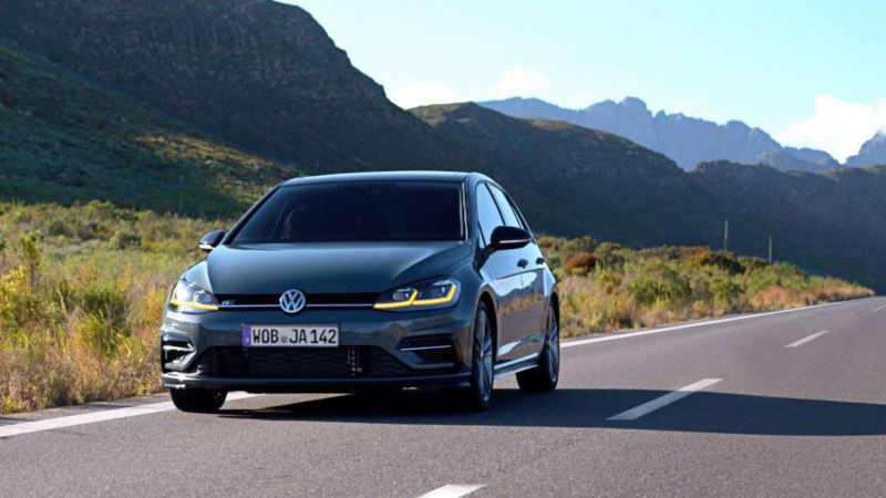 Volkswagen bil i trafik på väg. Berg syns i  bakgrunden.
