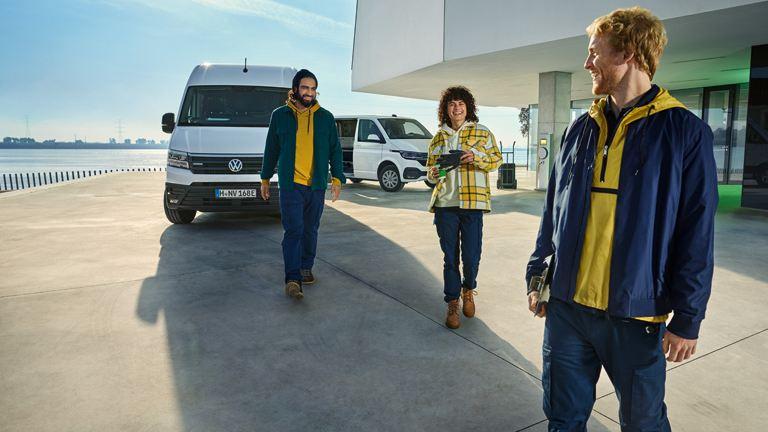 to menn og en dame som står på en brygge foran Volkswagen e-Crafter el varebil og Transporter varebil
