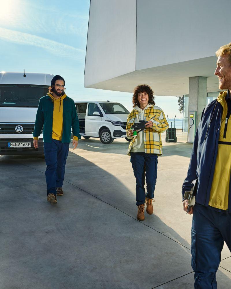 Un e-Crafter Volkswagen, un ABT e-Transporter e un ABT e-Caddy parcheggiati davanti a un complesso di edifici durante le operazioni di scarico.