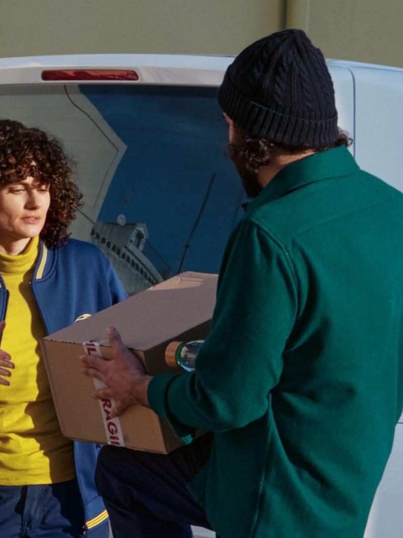 Due uomini caricano l'ABT e-Transporter 6.1.