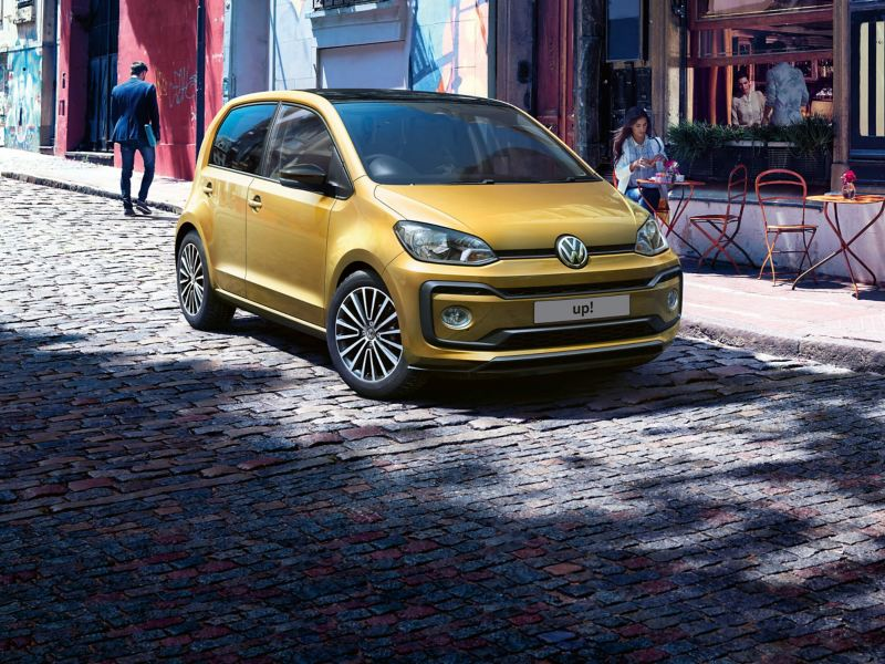 A gold Volkswagen up! Parked on a cobbled city street.
