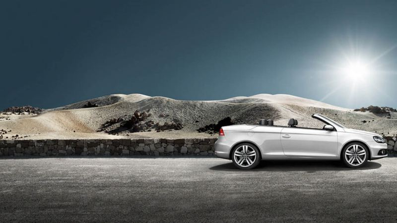A silver Volkswagen Eos, parked in the desert, the roof down.