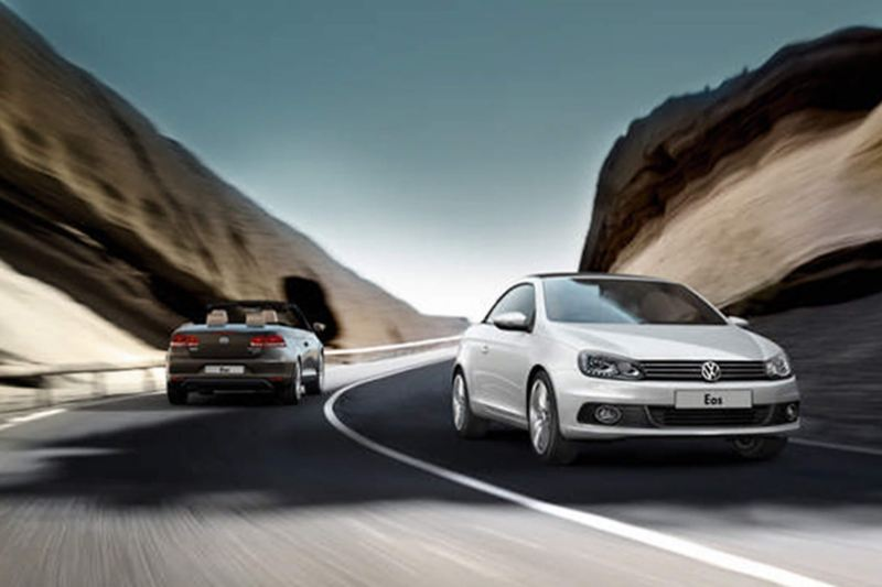 Two Volkswagen Eos' driving in opposite directions, through the mountains.