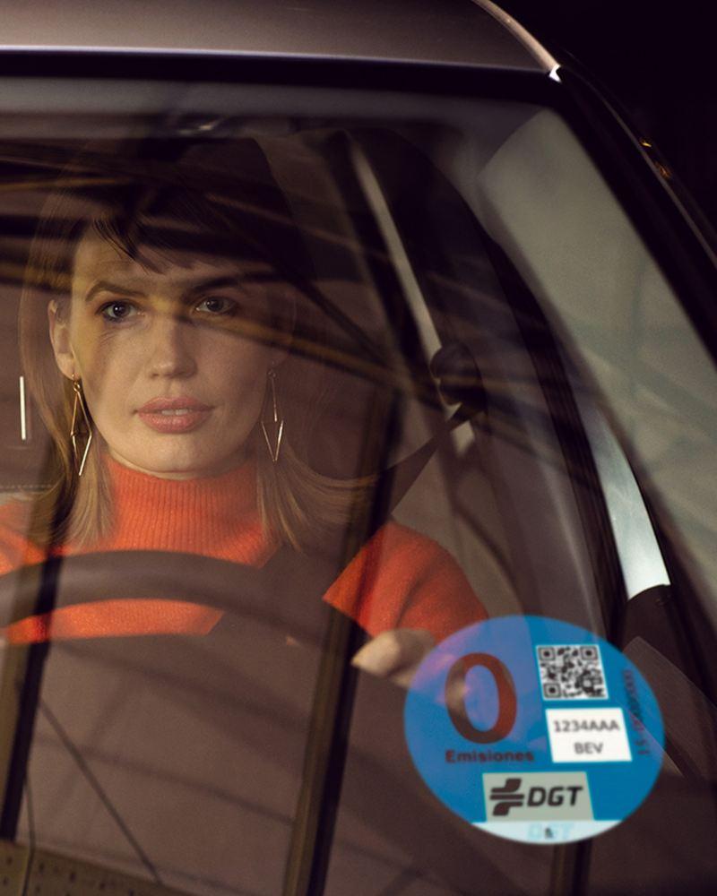 Mujer dentro de un e-Golf vista a través del parabrisa con una etiqueta de 0 emisiones de la DGT