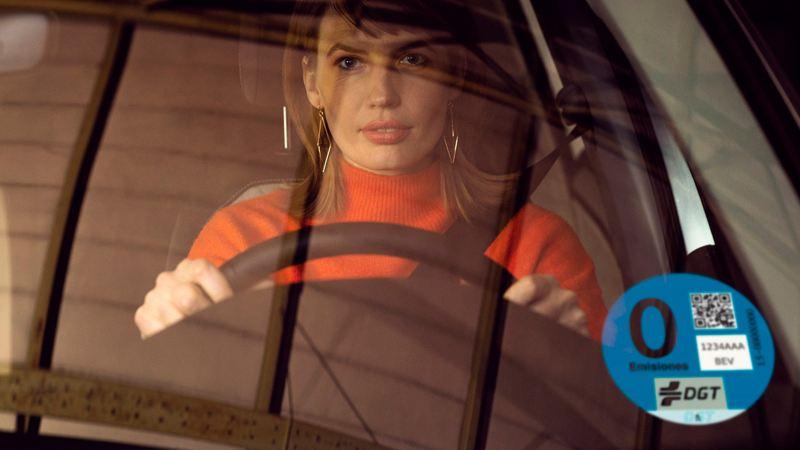 Mujer dentro de un e-up! vista a través del parabrisa con una etiqueta de 0 emisiones de la DGT