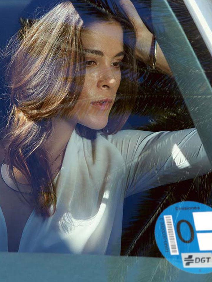 Mujer dentro de un ID.3 vista a través del parabrisa con una etiqueta de 0 emisiones de la DGT