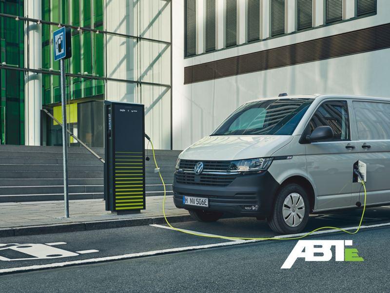 Ein ABT e-Transporter wird an einer Ladestation an einer Straße geladen.