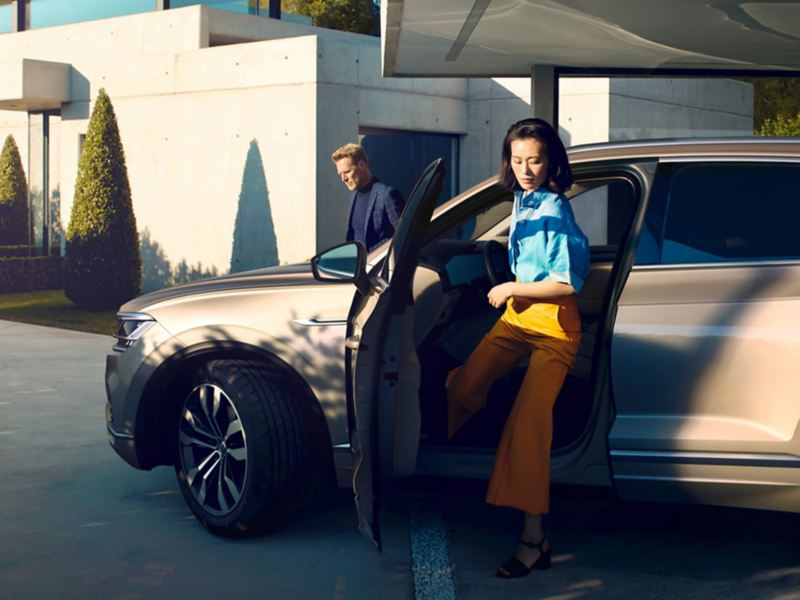 A couple getting out of a Volkswagen Touareg.