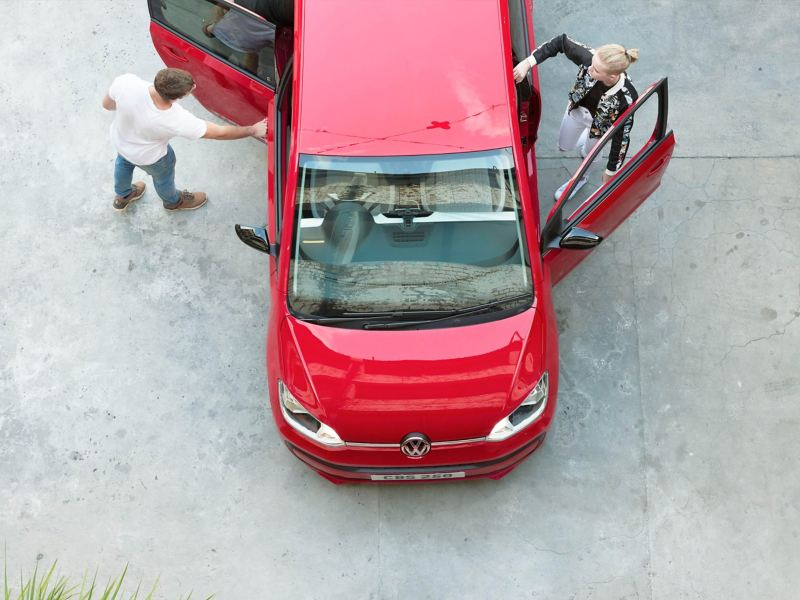 A group of friends getting into a red Volkswagen up!
