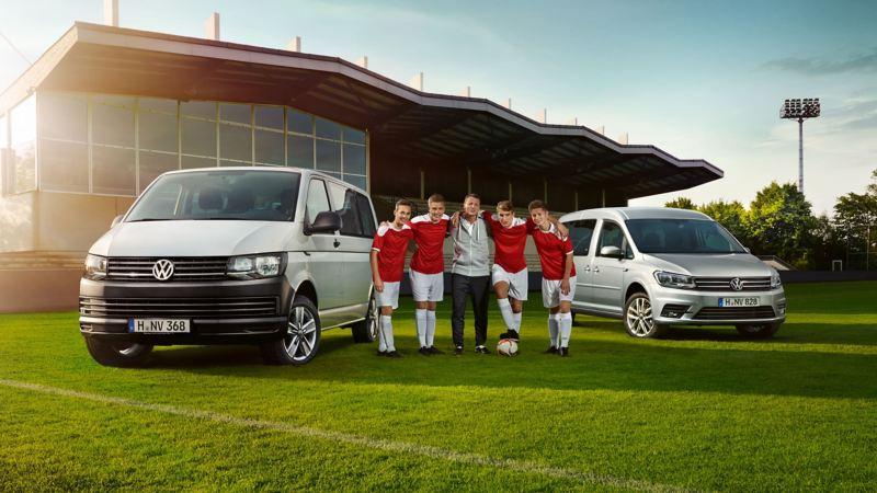 Transporter und Caddy auf einer Wiese, dazwischen vier Fußballspieler.