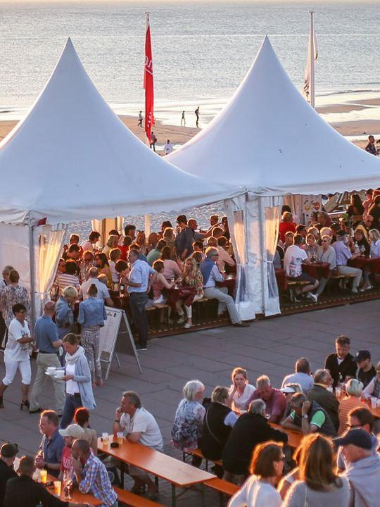 Am Strand sind weiße Zelte und Bierbänke aufgebaut: Menschen versammeln sich bei einem Surf-Wettbewerb.