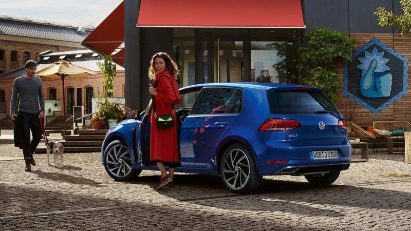 Eine Frau steht neben Ihrem blauen VW Golf auf der Strasse