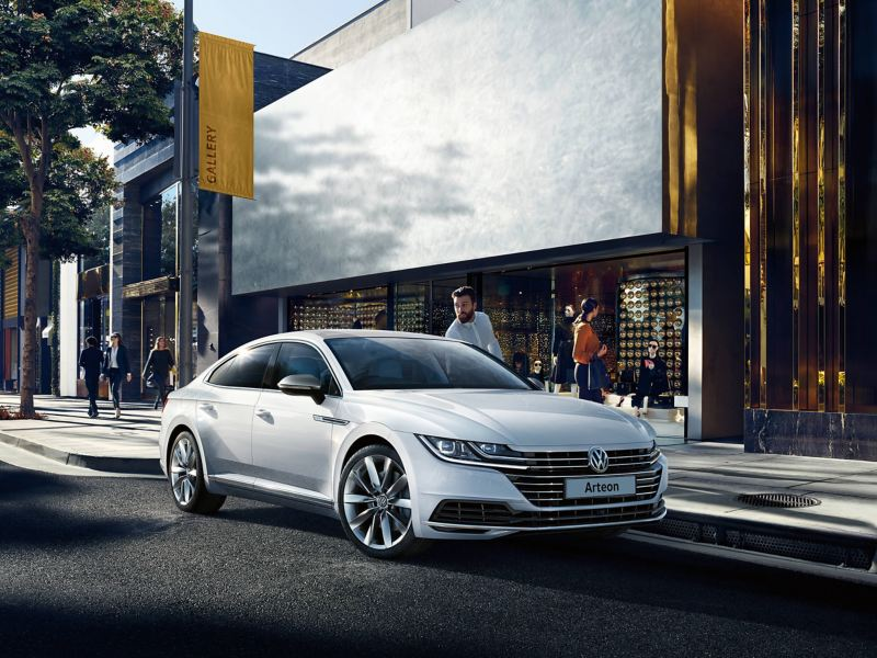 A white Volkswagen Arteon parked on a city street outside of shops, the owner getting in.