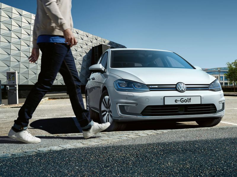 Man walking in front of a Volkswagen e-Golf car