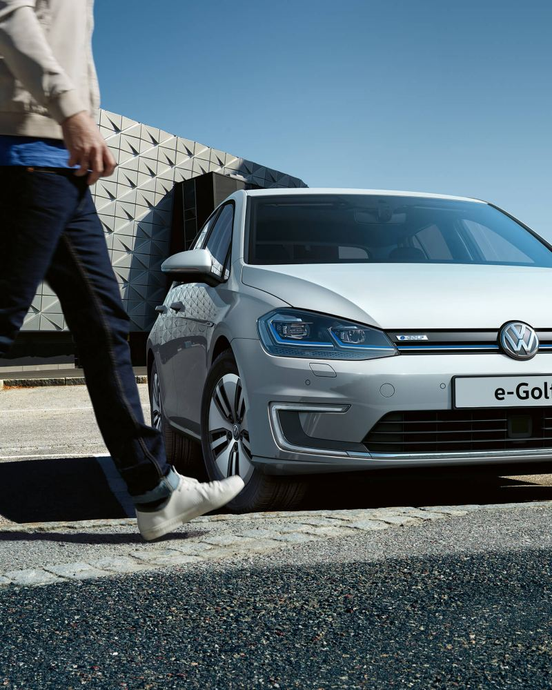 Man walking in front of a Volkswagen e-Golf