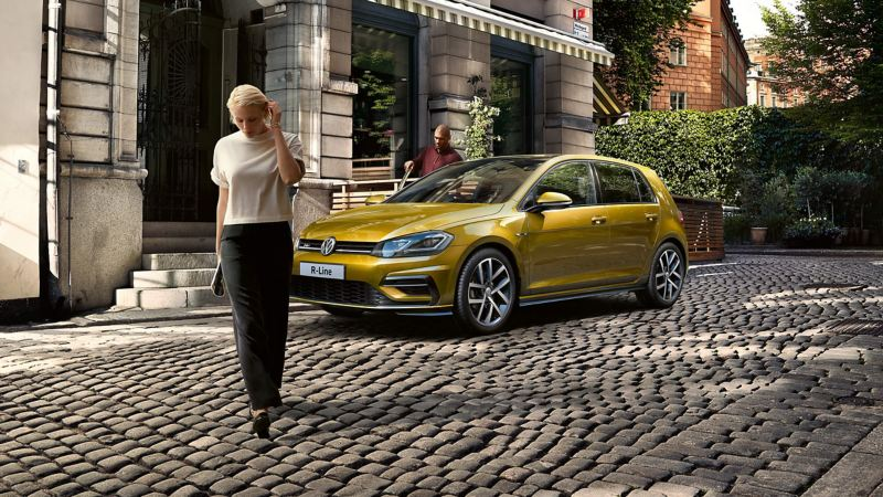 A lady walking in front of a Volkswagen Golf R-Line.