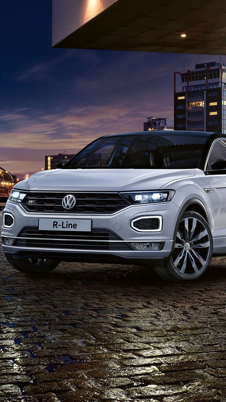 White Volkswagen T-Roc on a dark cobbled road.