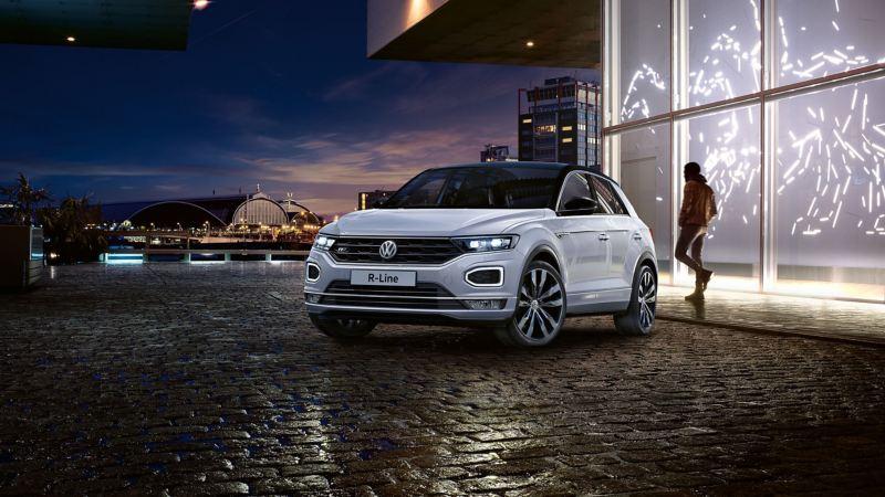 White Volkswagen T-Roc on a dark cobbled road.