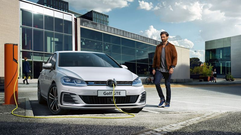 A man stood next to his white Golf GTE whilst it charges.