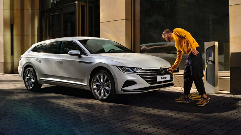 A man charging his Arteon Shooting Brake at the side of the road.