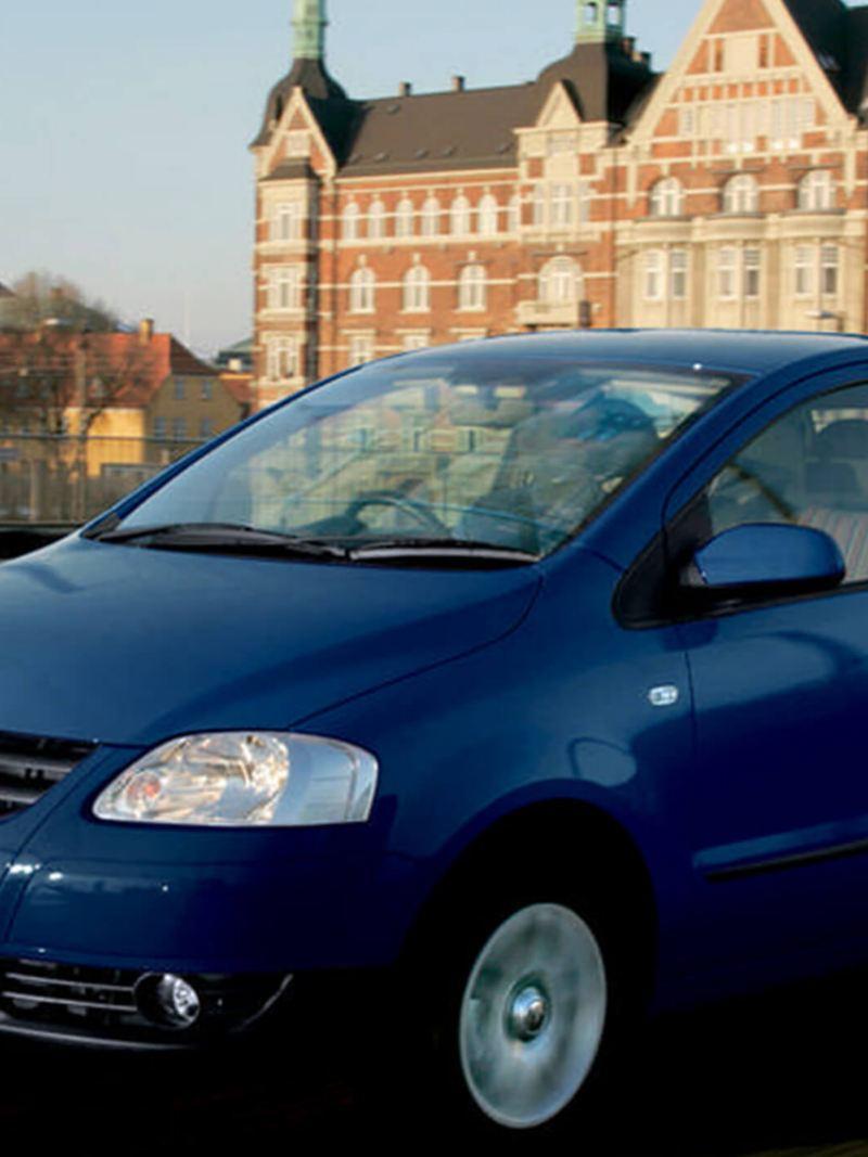 A blue Volkswagen Fox , driving across a bridge.