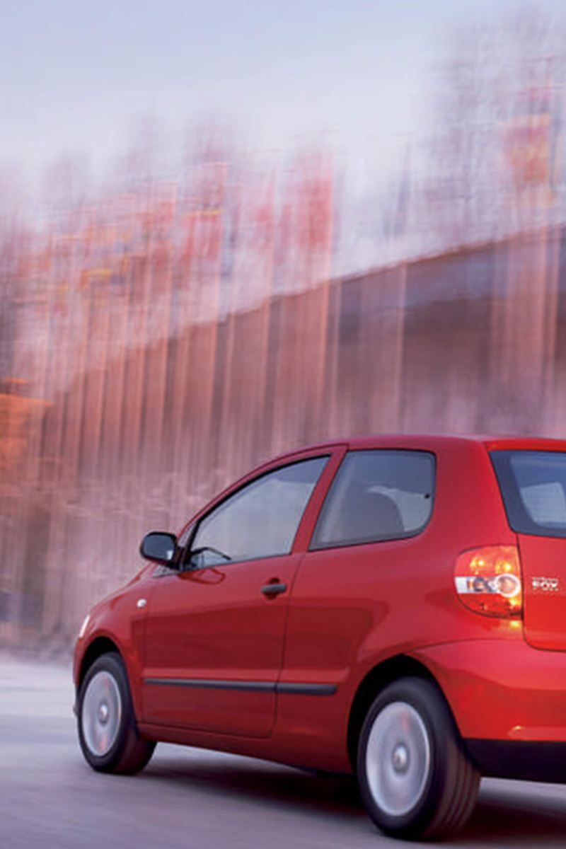 Rear view of a red Volkswagen Fox, in the snow.