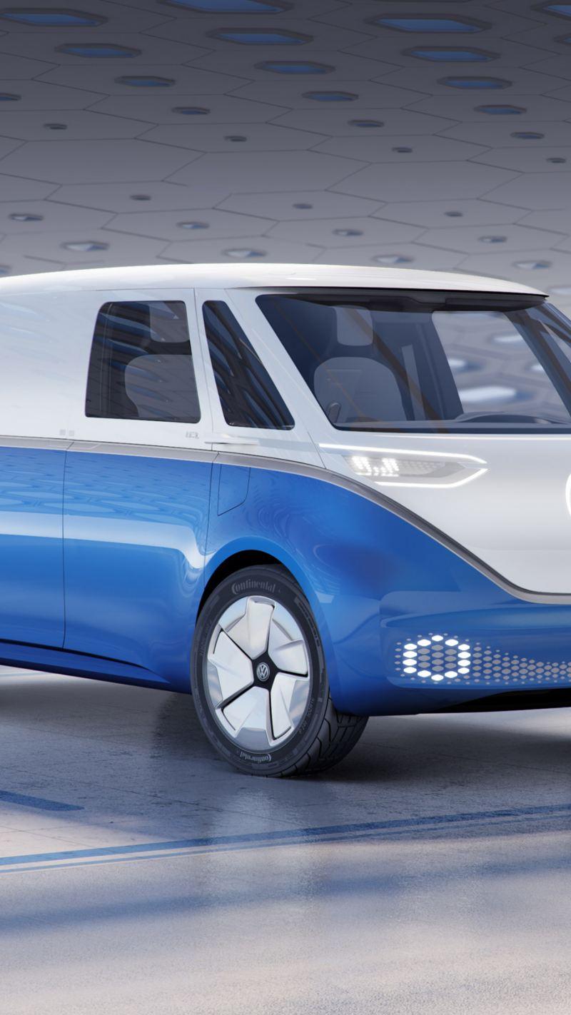 Bildet viser en hvit og blå Volkswagen ID. BUZZ cargo el varebil som står parkert mot hvit bakgrunn med LED hovedlys