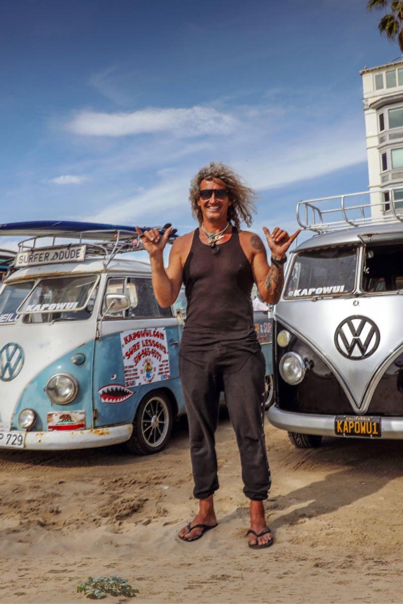 """Surfer Martin steht am Strand vor zwei alten Bullis. Er macht die """"Hang Loose""""-Geste."""