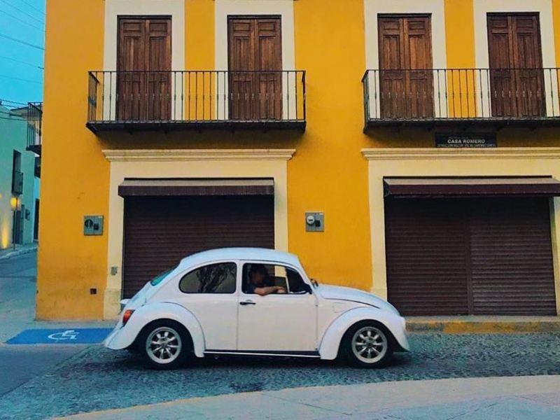 Vocho, el auto icónico Volkswagen estacionado afuera de edificio amarillo