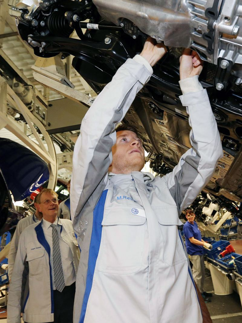 Marco Reus arbeitet am Unterboden eines Fahrzeuges