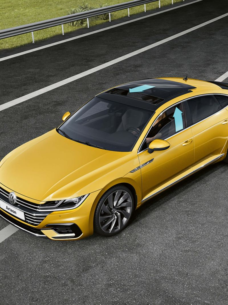 A yellow and a silver Volkswagen Arteon on the road with the sunroof and side front passenger windows open,