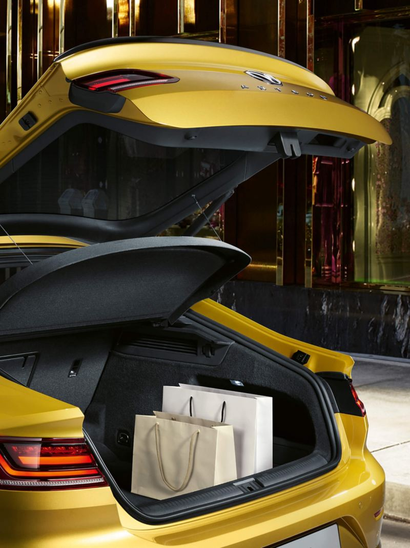 A yellow Volkswagen Arteon outside a shop with shopping bags inside the open boot.